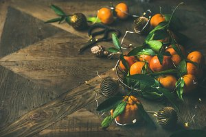 Fresh tangerines, decoration toys and light garland over rustic background