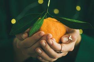 Tangerine fruit in hands of lady wearing green dress