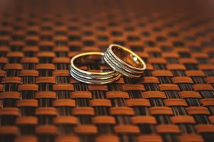 Two gold rings on wicker background