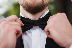Man with beard correcting his bowtie