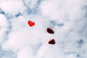 Heart shaped balloons against sky.