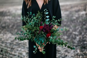 Girl holds bouquet of flowers and greenery