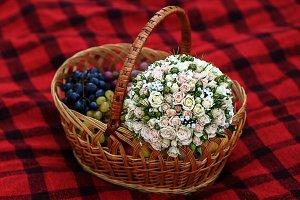boquet and different fruits in wicker basket