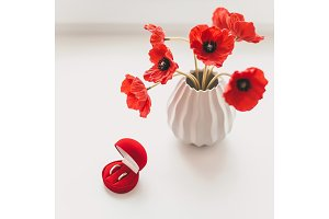 Wedding rings and vase with poppy flowers