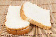 Sliced bread on the wooden plate.
