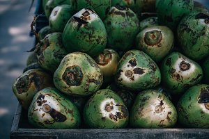 Green Coconuts Laying On Wood Cart