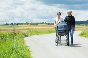 Grandparents Going For A Walk With Baby Stroller
