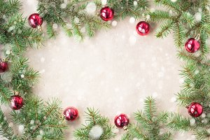Festive christmas border with red balls on fir branches and snowflakes with snow on rustic beige background