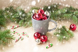 Silver and red christmas decorations balls in cup with fir tree and snow christmas background