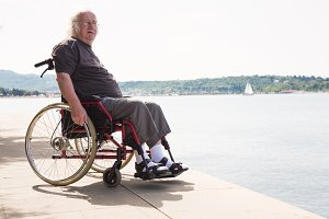 Happy Old Man In Wheelchair Looking At The Sea