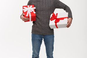 Christmas Concept - Happy young man with beard carries a lot of presents isolated on white background.