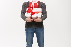Christmas Concept - young handsome man with beard holding heavy presents with exhausted facial expression on white background.