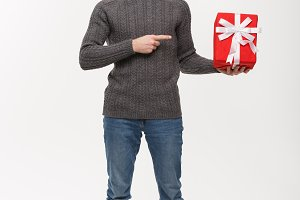 Christmas Concept - Happy young man with beard pointing finger present isolated on white background.