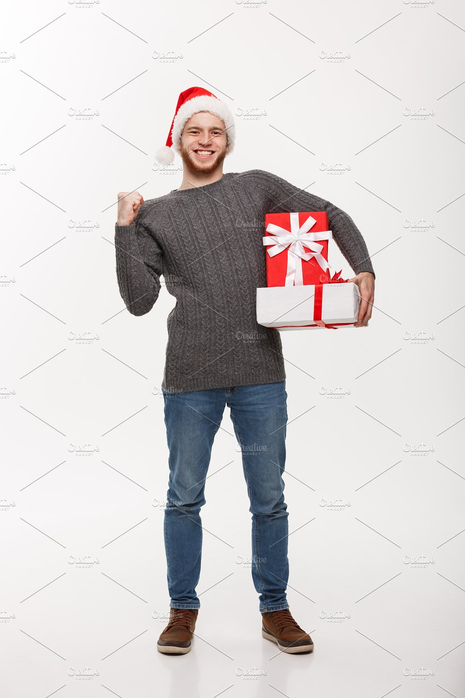 Christmas Concept Hy Young Man With Beard Holding Present And Hand Up Isolated On White Background