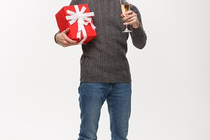 Christmas Concept - Happy young man with beard holding present and champagne celebrating for Christmas isolated on white background.