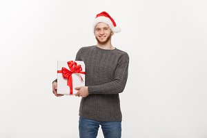 Christmas Concept - Happy young man with beard carries present on side isolated on white background.