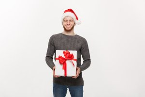 Christmas Concept - Happy young handsome man with beard giving presents to camera isolated on white background.