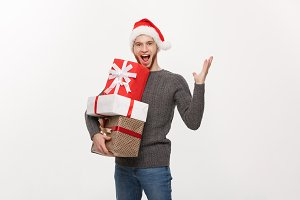 Christmas Concept - Happy young man with beard holding present and hand up isolated on white background.