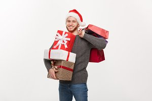Christmas Concept - young handsome man with beard holding a lot of presents and shopping bags with happy facial expression on white background.