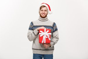 Christmas Concept - Happy young man with beard carries present isolated on white background.
