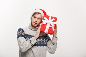 Christmas Concept - Happy curious young man with beard carries present and listen inside the box isolated on white background.
