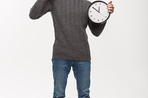 Holiday concept - Young handsome beard man in sweater with white clock giving ok sign.
