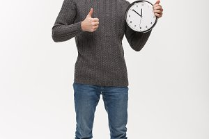 Holiday concept - Young handsome beard man thumb up on white clock.
