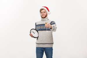 Holiday concept - Young handsome beard man in sweater with white clock and champagne over white studio background.