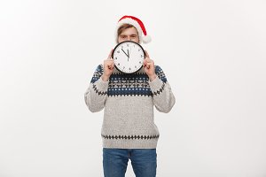 Holiday concept - Young handsome beard man hidden behind white clock over white studio background.