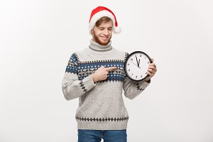 Holiday concept - Young handsome beard man pointing on white clock telling the time.