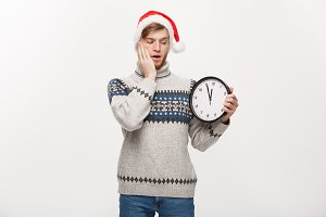 Holiday concept - Young happy handsome beard man in sweater holding white clock over white studio background.