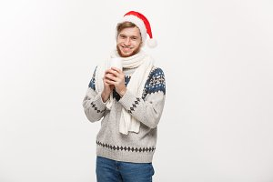 Christmas concept - Young beard man in sweater and santa hat holding a hot coffee cup isolated on white with copy space.
