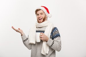 Christmas concept - Young beard man in sweater and santa hat holding a hot coffee cup pointing hand on side isolated on white with copy space.