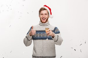 Chirstmas Concept - Happy young caucasian beard man holding champagne glass with confetti background celebrating for Christmas day.