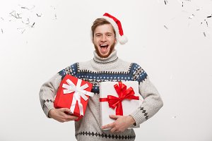 Chirstmas Concept - Happy young caucasian beard man holding present box with confetti background celebrating for Christmas day.