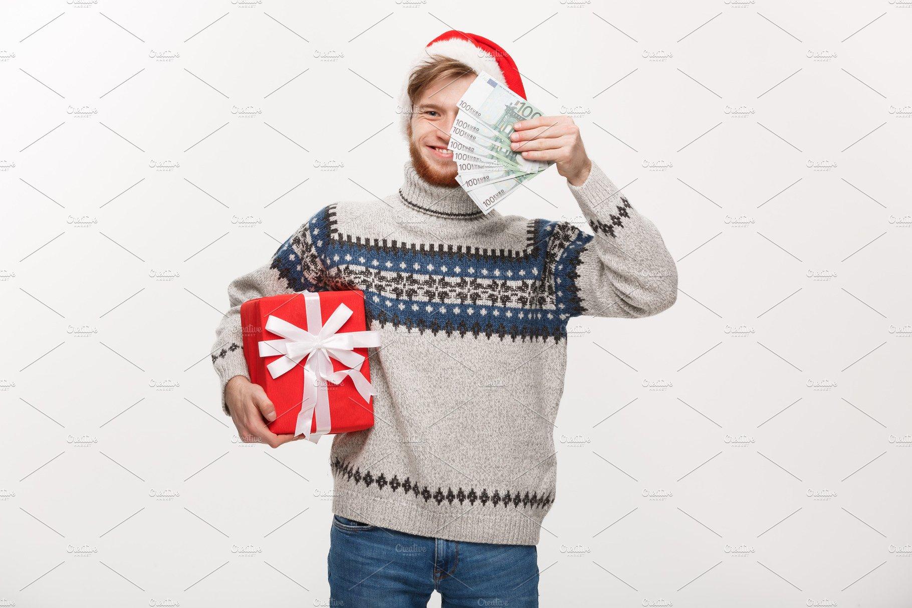 Holiday Concept - Young beard man holding christmas gift and ...