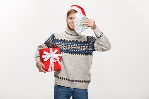 Holiday Concept - young beard man holding a christmas gift box and money over white background