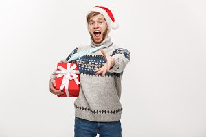Holiday Concept - Young beard man holding christmas gift and throwing money to camera.