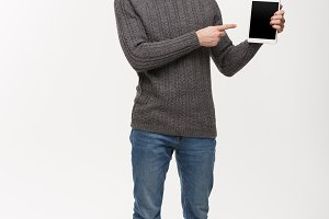 Holiday and Business Concept - Young handsome man showing tablet display and pointing finger presenting.