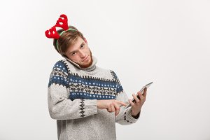 Holiday and Business Concept - Young handsome man busy working on phone and digital tablet.