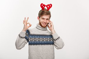 Holiday and Business Concept - Young handsome man talking on phone and giving ok sign.