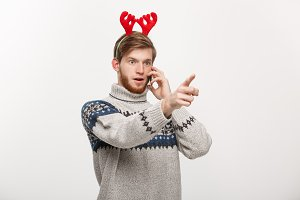 Holiday and Business Concept - Young handsome man talking on phone and pointing finger in front.