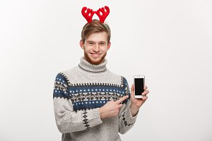 Holiday and Business Concept - Young handsome man showing mobile phone display and pointing finger presenting.