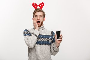 Holiday and lifestyle concept - young beard handsome man surprising with something in mobile phone.