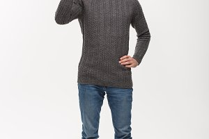 Holiday Concept - Young beard man in sweater giving ok sign to camera.