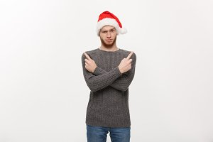Holiday Concept - Young beard man in sweater enjoy playing and pointing finger onside with copyspace.