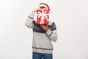 Holiday Concept - young handsome man hiding himself behind present.