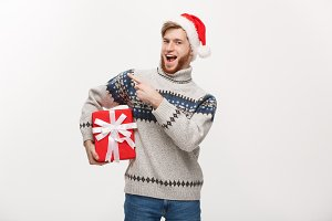 Holiday Concept - Young beard man in sweater holding box and pointing hand on side.