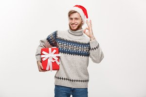 Holiday Concept - Young beard man in sweater holding box and giving ok sign.