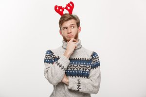 Holiday Concept - Young beard man in sweater with thoughtful gesture on white background.